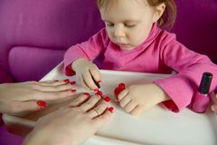 The child paints the nails of his mother with varnish royalty free stock image