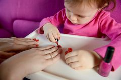 The child paints the nails of his mother with varnish stock photography