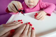 The child paints the nails of his mother with varnish royalty free stock photo
