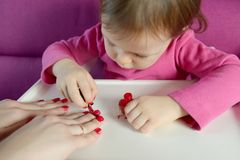 The child paints the nails of his mother with varnish royalty free stock images