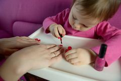 The child paints the nails of his mother with varnish stock image