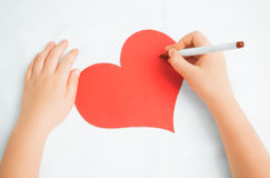 Child paints on a paper heart Royalty Free Stock Photo
