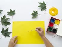 Child paints a picture of autumn leaf with paints royalty free stock image