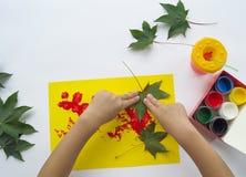 Child paints a picture of autumn leaf with paints stock photos