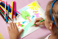 Child paints a picture of pencils about protecting nature. Royalty Free Stock Photography