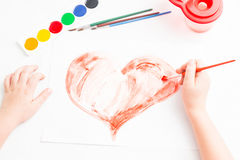 Child paints a red heart Stock Photography