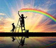 Child paints the seascape with a rainbow Stock Images
