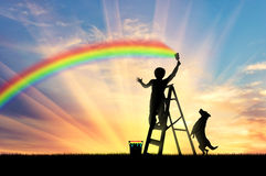Child paints the seascape with a rainbow Stock Image