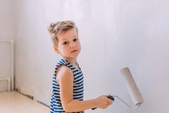Five-year-old boy paints the wall with white paint Royalty Free Stock Images