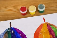 The child paints in watercolor, painting. Children`s drawing. Multicolored. Album for drawing. Kindergarten and school royalty free stock image
