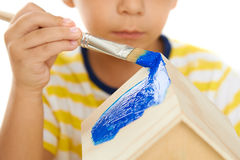 Child paints wooden birdhouse Royalty Free Stock Images