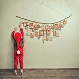 Child in pajamas and Christmas cap stretches for advent calendar with small gifts. kid counts days until new year.  royalty free stock images