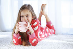 Child in pajamas. Portrait of child in soft warm pajamas lying down on the carpet at home Stock Images