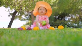 Child in panama having fun outdoor on back yard. Happy childhood concept. Baby girl playing with fruits outdoor. Toddler. Baby girl sitting on green grass on stock video footage