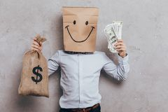 Child with paper bag on head cash and money bag. Isolated on grey Stock Images