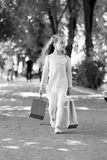 Child with paper bags in summer. Girl with shopping bags walk in park. Kid shopper in fashion clothes outdoor. Shopping. On sale and purchase. Little princess stock image