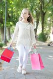 Child with paper bags in summer. Girl with shopping bags walk in park. Little princess with crown on long blond hair. Shopping on sale and purchase. Kid royalty free stock image