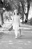 Child with paper bags in summer. Girl with shopping bags walk in park. Little princess with crown on long blond hair. Kid shopper in fashion clothes outdoor royalty free stock image
