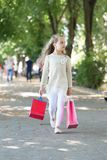 Child with paper bags in summer. Girl with shopping bags walk in park. Kid shopper in fashion clothes outdoor. Shopping. On sale and purchase. Little princess royalty free stock photo
