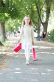 Child with paper bags in summer. Girl with shopping bags walk in park. Little princess with crown on long blond hair. Kid shopper in fashion clothes outdoor stock photo