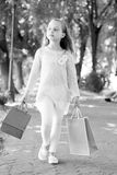 Child with paper bags in summer. Girl with shopping bags walk in park. Little princess with crown on long blond hair. Shopping on sale and purchase. Kid stock photos