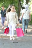 Child with paper bags in summer. Shopping on sale and purchase. Girl with shopping bags walk in park. Little princess. With crown on long blond hair. Kid stock photo
