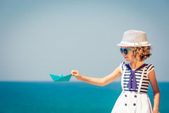 Child with paper sailing boat on summer vacation Royalty Free Stock Image
