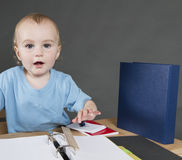 Child with paperwork at small desk Stock Photography