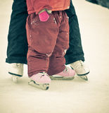 Child and parent feet on skates Stock Photos