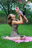 Child and parenthood concept - happy mother with little baby sitting on blanket in park Stock Image