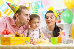 Child with parents blow candle on birthday cake Royalty Free Stock Image