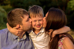 Child with parents embracing and kissing. Royalty Free Stock Photography