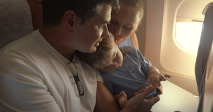 Child with parents traveling by plane. Young parents and little son traveling by air. Child playing game on fathers smart phone to entertain himself during the stock video footage