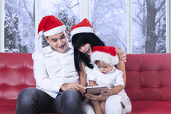 Child with parents using tablet on sofa Royalty Free Stock Image