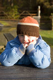Child in park. Little boy sitting in the park holding hands to head looking frustrated Royalty Free Stock Photography