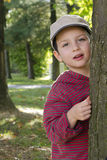 Child at park or forest. Portrait of a child boy peeking from behind a tree in a park or forest Royalty Free Stock Images