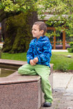 Child in park or garden. Child boy sitting on a fountain pond in a park or garden Stock Images