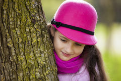 Child at the park. Child peeking behind a tree Stock Photos