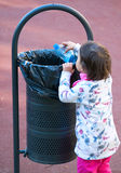 Child participate in recycling while putting a plastic bottle in the trash Royalty Free Stock Images