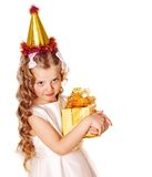 Child in party hat with gold gift box . Stock Photo
