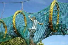 The child passes through the mesh. Playground Royalty Free Stock Photo