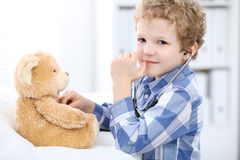 Child  patient afrer health exam playing as a doctor with stethoscope and teddy bear Stock Image