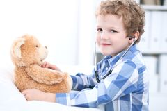 Child  patient afrer health exam playing as a doctor with stethoscope and teddy bear.  Stock Photography