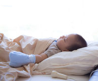 Child patient asleep in hospital bed. 5 months old sick baby with viral infection, receiving infusion therapy while asleep in hospital bed Stock Photos