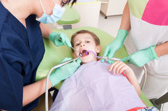 Child patient drilling procedure in dental office. Relaxed child patient having drilling procedure in dental office sitting in dentist chair with no fear Royalty Free Stock Photos