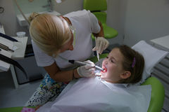 Child patient on her regular checkup. Child patient in paediatric dentists office on her regular checkup for tooth decay, caries and gum disease. Early Royalty Free Stock Images