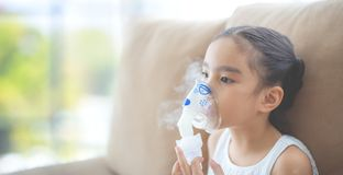 Child patient inhalation therapy by the mask of inhaler with soft stream smoke from bronchodilator. royalty free stock images