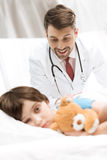 Child patient lying in bed with smiling doctor behind. Upset child patient lying in bed with smiling doctor behind Royalty Free Stock Photos