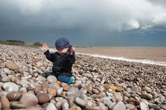 Child on a pebble beach in Devon, England Stock Photo