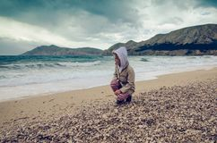 Child on the pebble beach stock image